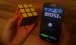 A Rubik's Cube and a phone's stopwatch app showing the time 00:03:53:93