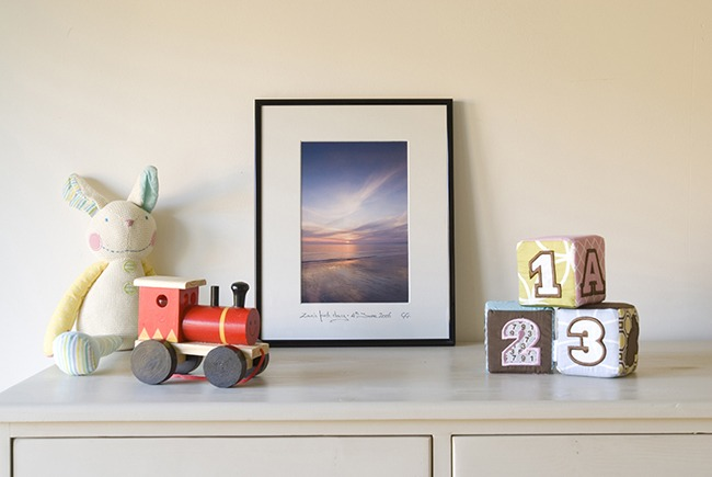 A framed picture of a beautiful sunrise next to some traditional baby gifts.