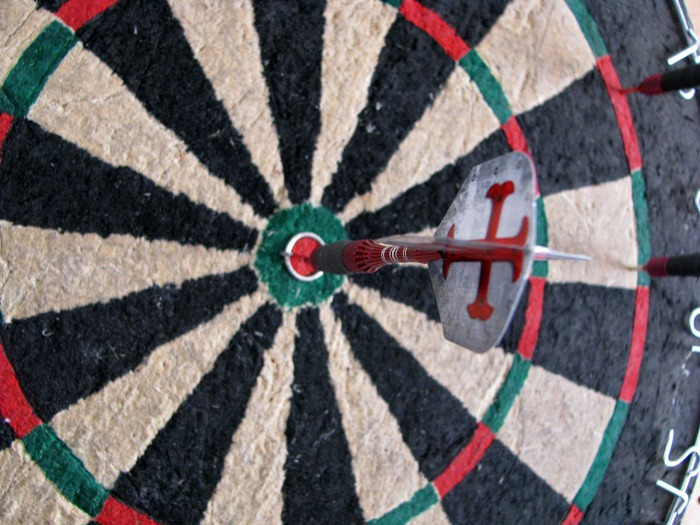 Close-up image of a dart board with a dart in the bullseye
