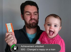 A man holding a train ticket and a baby with a video game achievement graphic superimposed.