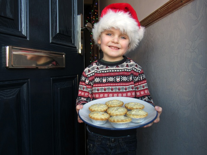 A young boy demonstrating one of the five ways to make your home more welcoming to guests at Christmas - offering mince pies!