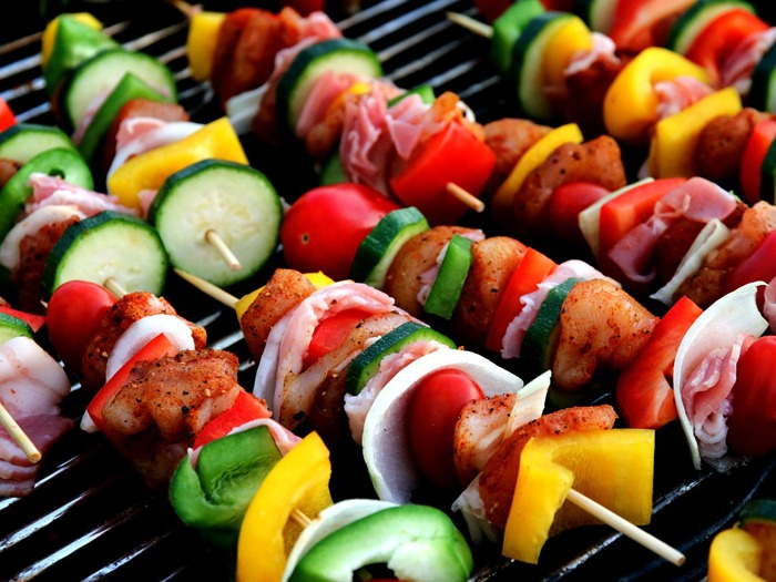 Meat and veggie skewers cooking on a perfect bbq.