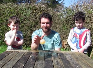 A man and his sons dropping an egg as part of a BBC Terrific Scientific experiment.