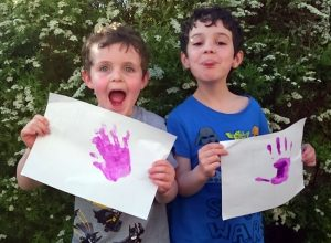 Two young boys with purple hand prints.
