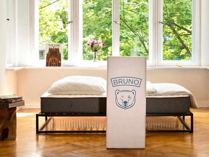 A bed with a Bruno Mattress box in front of it.