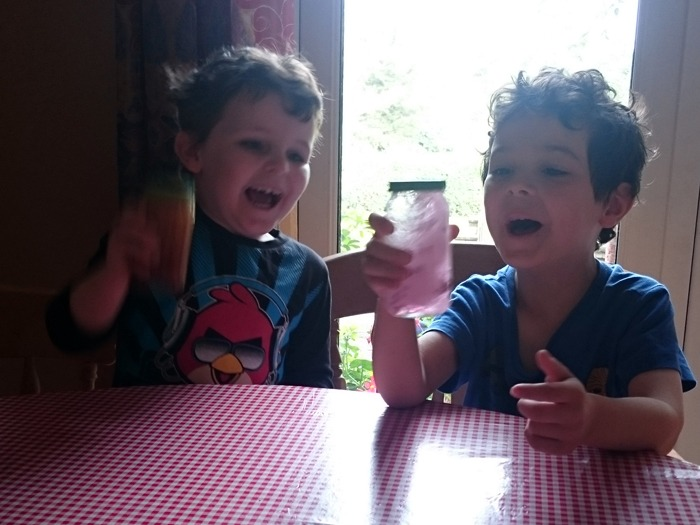 Two boys shaking jars of different coloured liquids.