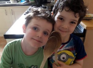 Two young boys holding up wooden spoons they found as part of a scavenger hunt.