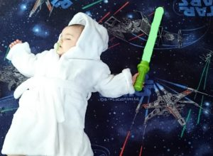 A sleeping baby dressed up as a Jedi on a Star Wars carpet.