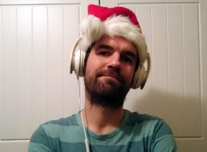 A grumpy looking man in a Santa hat and headphones.