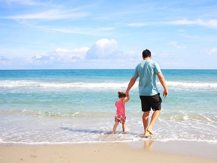 A father and child walking on a beach.