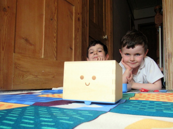 Two boys watching Cubetto.