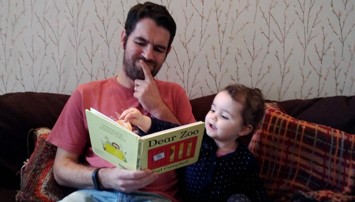 A father and daughter reading a copy of Dear Zoo.