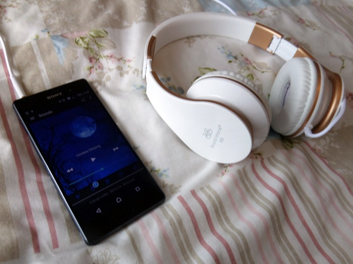 A smartphone running an app next to a pair of headphones.