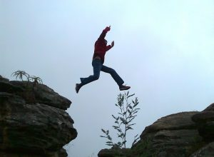 A man jumping across a chasm.