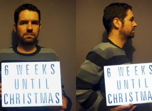 Mugshot-style photos of a man holding a lightbox with a countdown to Christmas. It gets earlier every year...