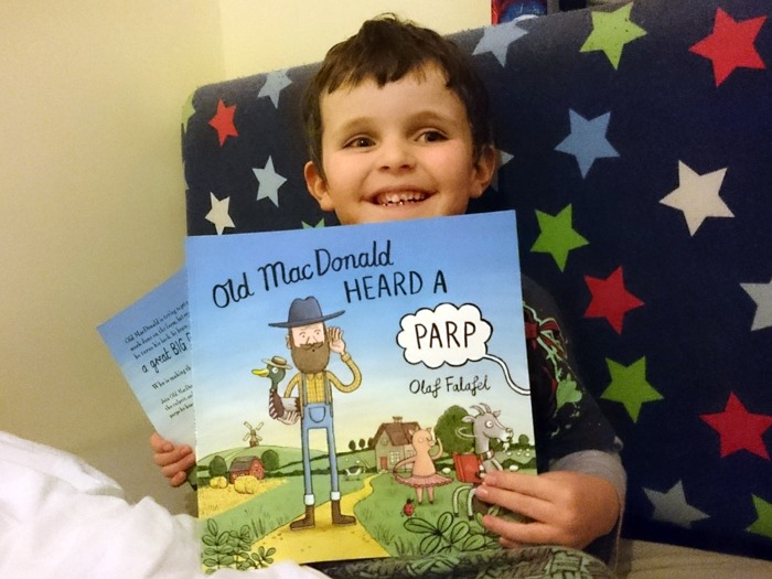 A young boy holding a copy of Old MacDonald Heard a Parp.