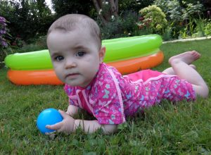 A baby girl sat in front of a paddling pool.