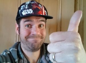 A man wearing a Star Wars hat and pretending to look pleased about it. The farce awakens.