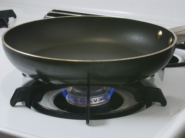 A frying pan on a gas hob.