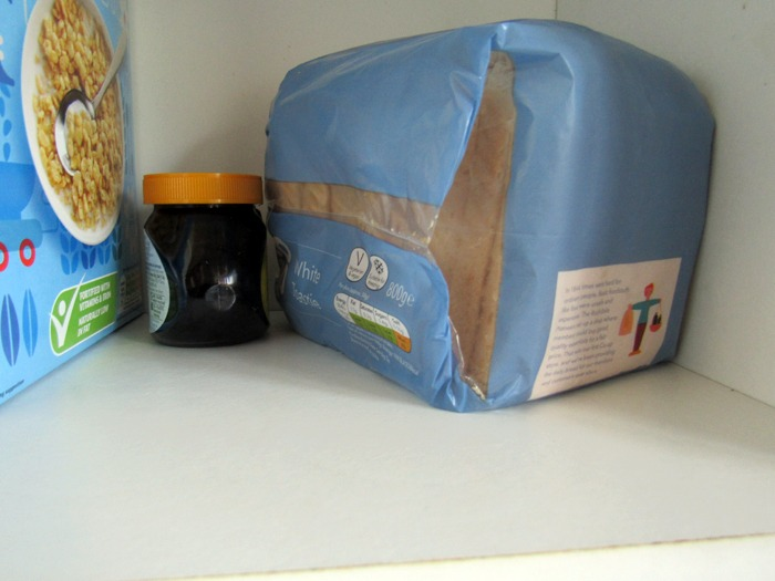 A loaf of bread alongside some other items in a food cupboard.