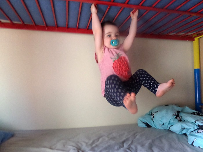 A toddler swinging from a bunk bed as if competing in hang tough in Gladiators.