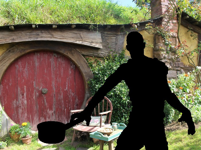 A silhouette of a zombie with a saucepan in front of a Hobbit-style house.