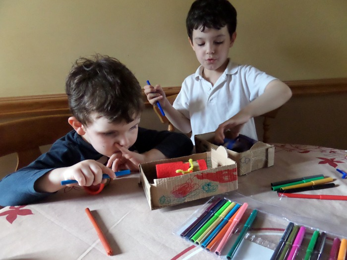 Two boys colouring in a cardboard bed they have made for a toy.