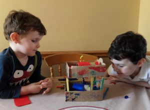 Two boys looking at some items they've made with the contents of their craft box.