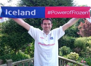 A man wearing an Iceland T-shirt and holding an Iceland flag.