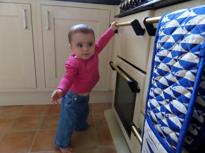 A baby standing next to a switched-off oven. Looking more 'Swan Lake Off' than Bake Off.