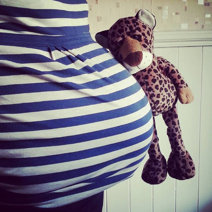 A pregnant woman holding a toy leopard of the same size as her bump.