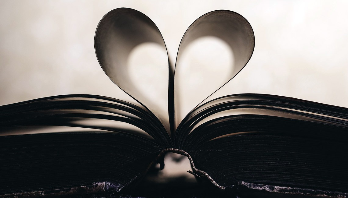 A book with two pages positioned in a heart shape.