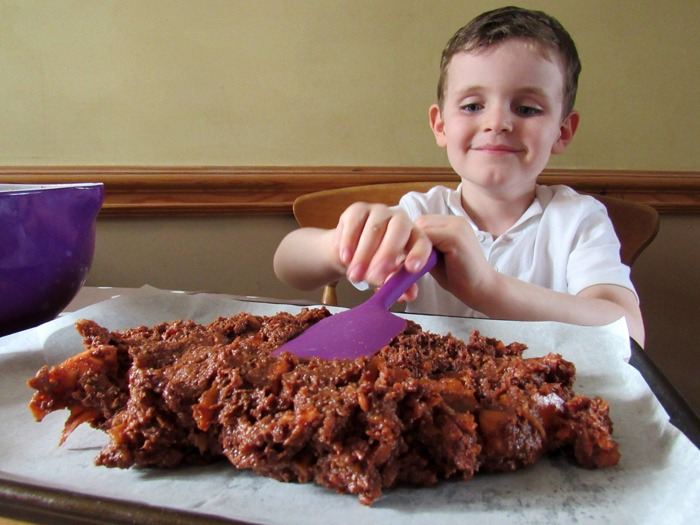 A young boy flattening chocolate brownie mix on a baking tray.