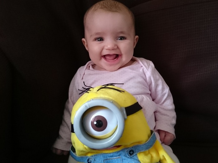 A smiling baby girl with a Minion toy.