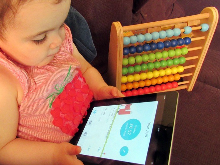 A toddler holding a tablet with the Moneybox Junior ISA app.