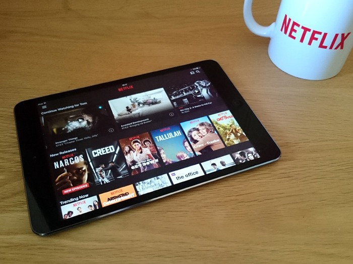 A tablet with Netflix loaded and a Netflix mug.