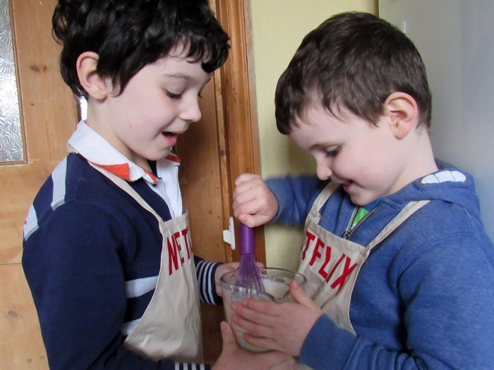 Two boys stirring a jug of pancake mixture.
