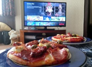 Some pizzas in front of a television screen showing Netflix.