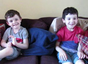 Two boys on a sofa talking about how to get to know dad.