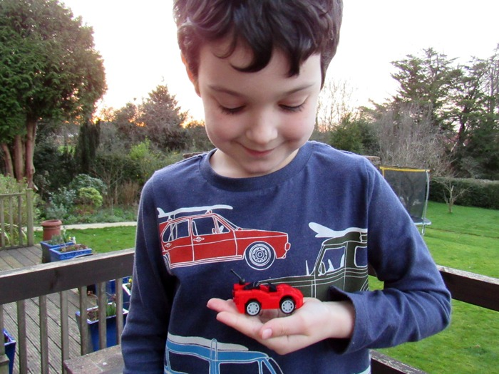 A young boy holding a toy car.
