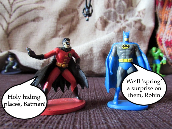 Batman and Robin figures on a sofa.