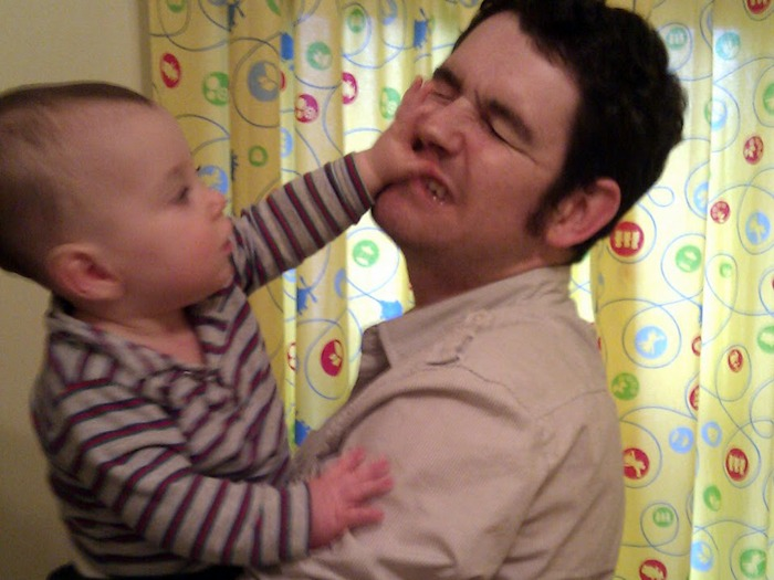 A typical parent having their face grabbed by a one-year-old child.