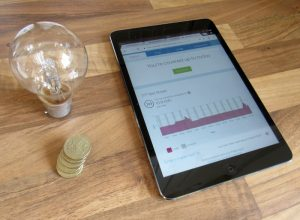 A lightbulb, some pound coins and the Powershop UK desktop screen illustrating the saving of electricity.