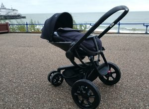 A pushchair in front of a seaside background.