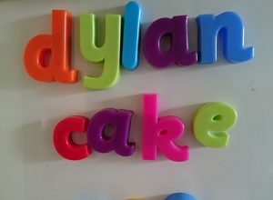 """Some magnetic letters spelling out the words: """"Dylan"""", """"cake"""" and """"poo""""."""
