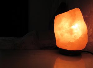 A Himalayan salt lamp on a bedside table with a bed in the background.