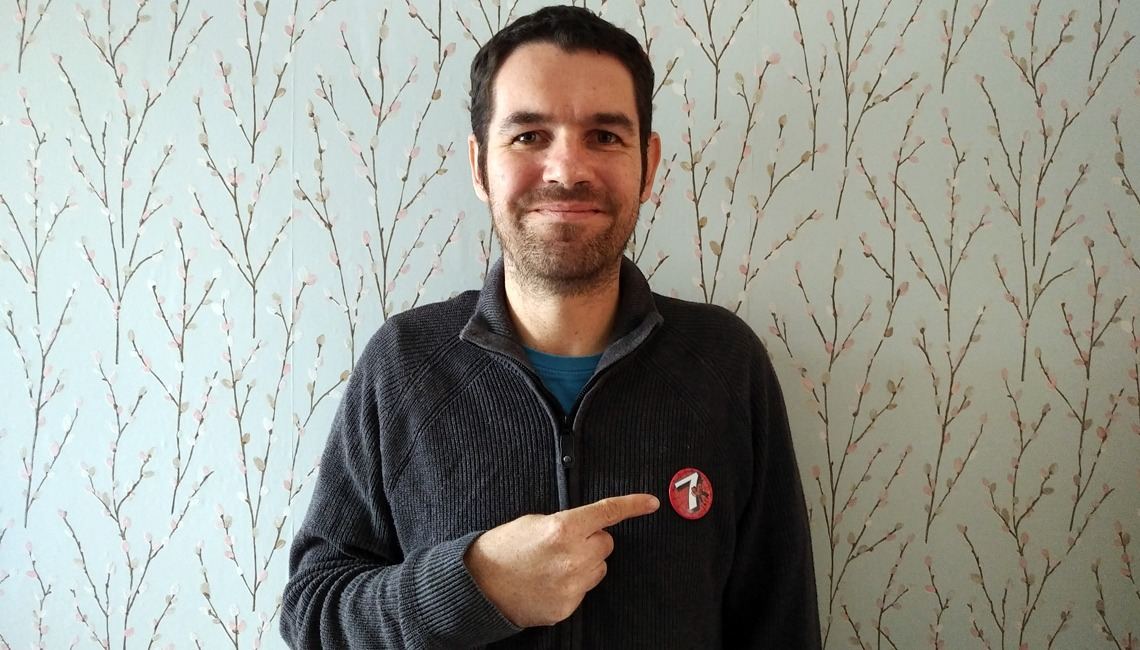 A man pointing at a badge with the number seven on it.