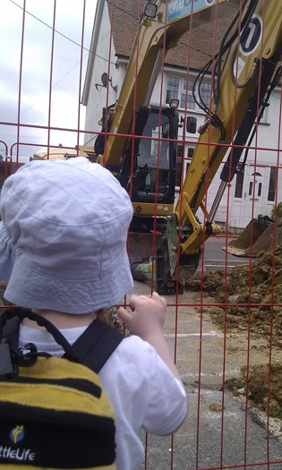 A Silent Sunday photo of a toddler looking at a digger.