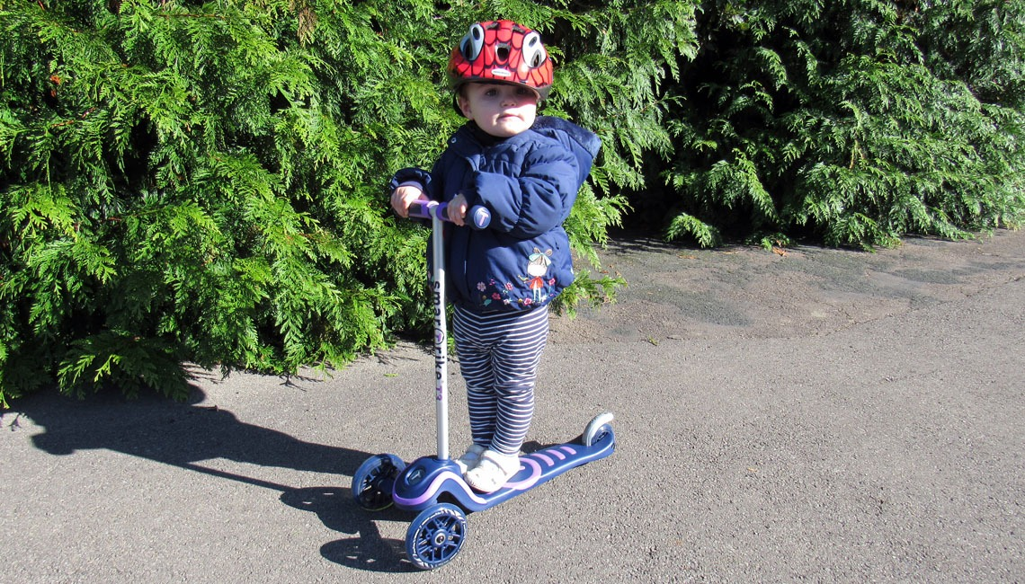 A toddler riding a SmarTrike T3 T-Scooter.