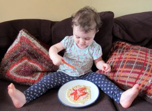 A toddler eating a pancake with The Super Yummies Dairy Pot and strawberries.